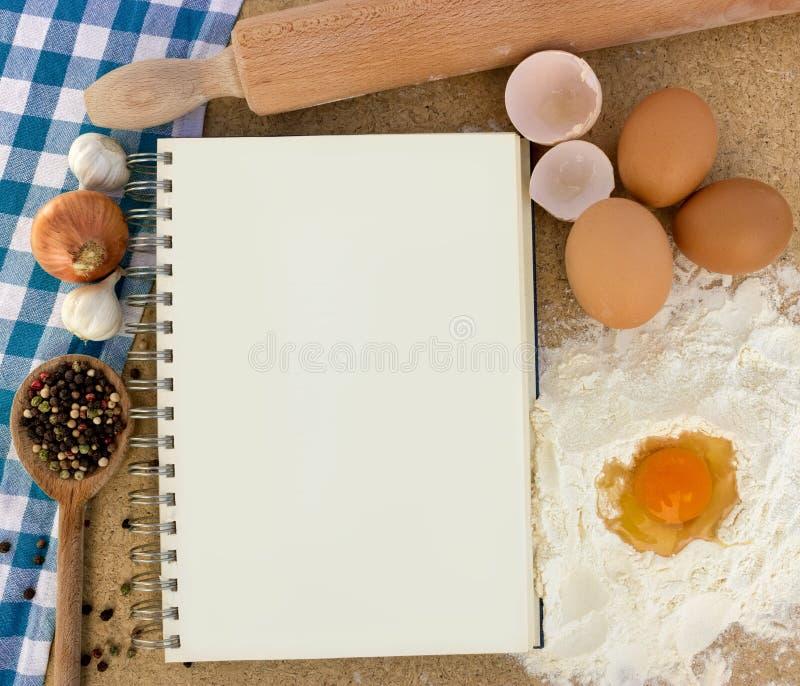 Livro de receitas com os ingredientes para cozer foto de stock