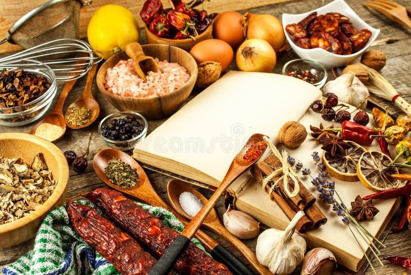 Livro de receitas e especiaria em uma tabela de madeira Preparação de alimento Um livro velho na cozinha Receitas para o alimento fotografia de stock royalty free