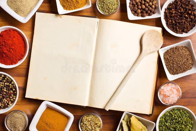 Livro de receitas e várias especiarias e ervas. imagens de stock