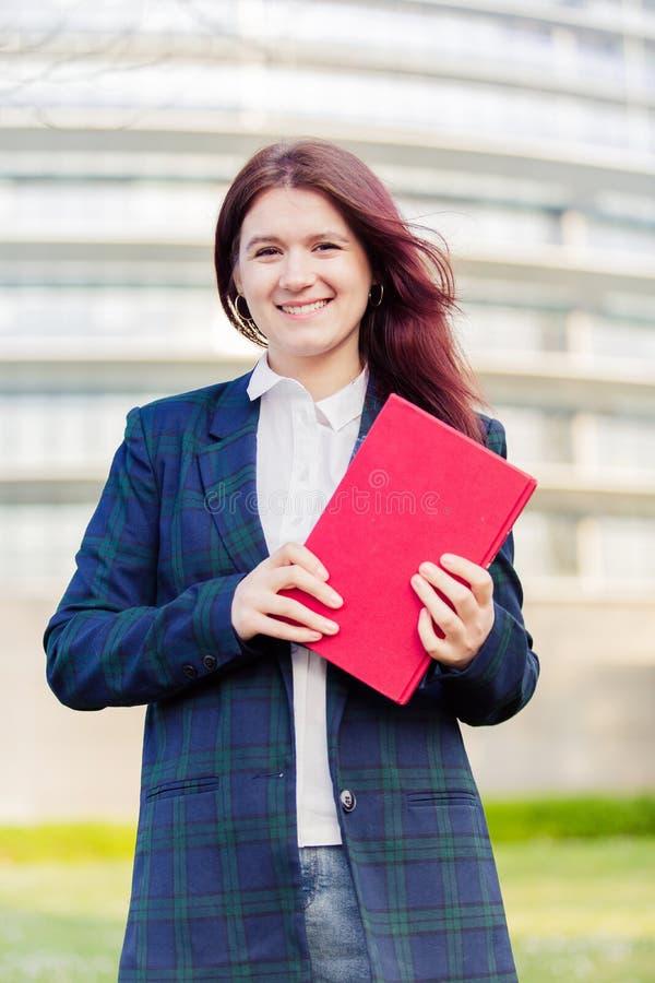 Livro de sorriso da terra arrendada do ar livre do estudante fotos de stock royalty free