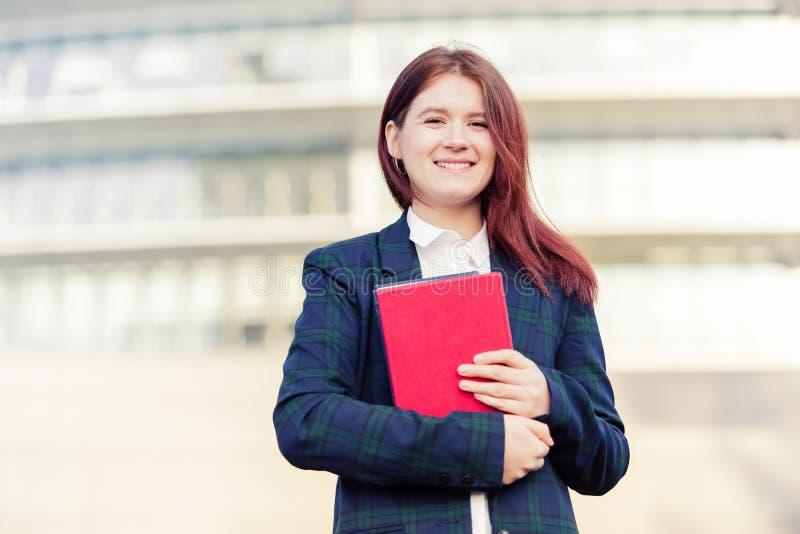 Livro de sorriso da terra arrendada do ar livre do estudante imagem de stock
