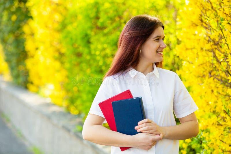 Livro de sorriso novo da terra arrendada do ar livre do estudante fotos de stock