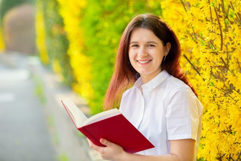 Livro de sorriso novo da terra arrendada do ar livre do estudante imagem de stock royalty free