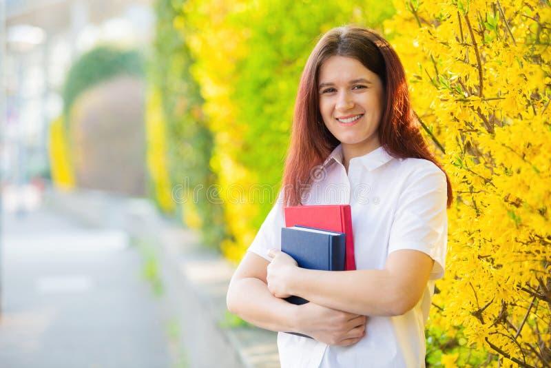 Livro de sorriso novo da terra arrendada do ar livre do estudante foto de stock royalty free
