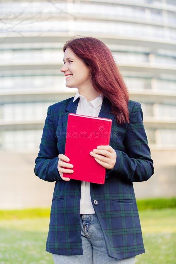 Livro de sorriso novo seguro da terra arrendada do ar livre do estudante imagem de stock royalty free