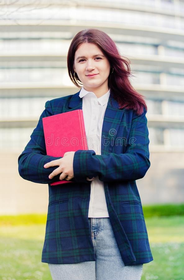Livro de sorriso novo seguro da terra arrendada do ar livre do estudante fotografia de stock
