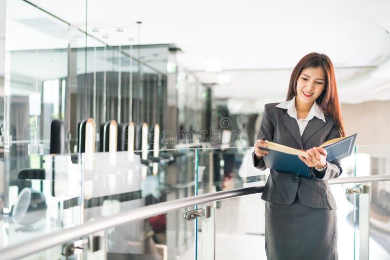 Livro de texto asiático da leitura da mulher de negócios ou do professor da faculdade no conceito moderno do escritório, do negóc fotografia de stock royalty free