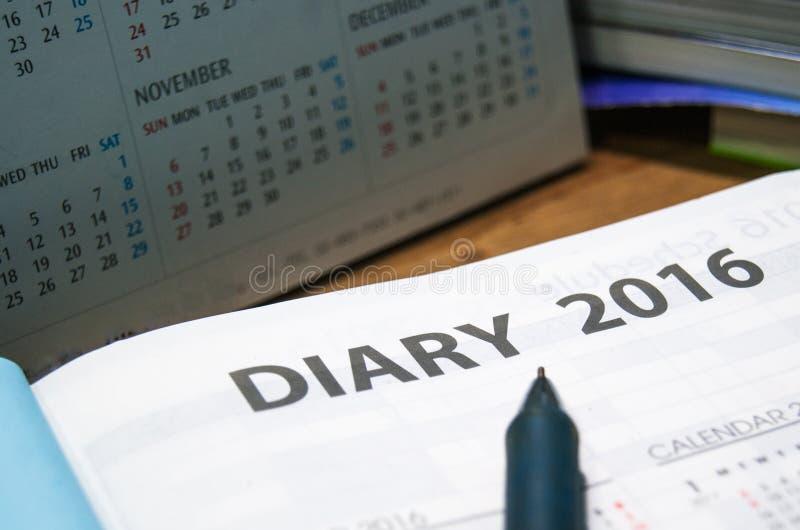 Livro diário do ano 2016 do planejador na tabela de madeira imagem de stock royalty free