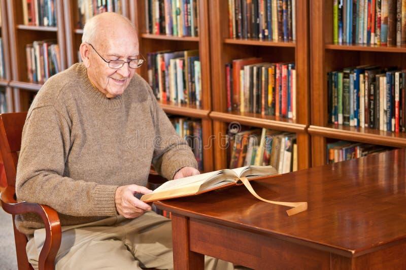 Livro do assento e de leitura do homem na tabela da biblioteca imagem de stock