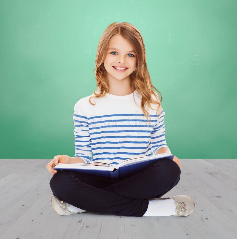 Livro do estudo e de leitura da menina do estudante foto de stock