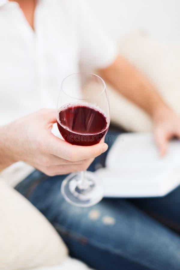 Livro do holdind da mão e vidro masculinos do vinho tinto imagens de stock