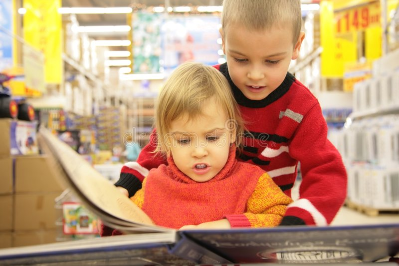 Livro do olhar de duas crianças na loja fotos de stock royalty free