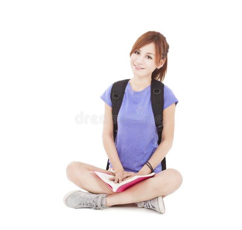 Livro e assento de leitura asiático da menina do estudante no assoalho foto de stock