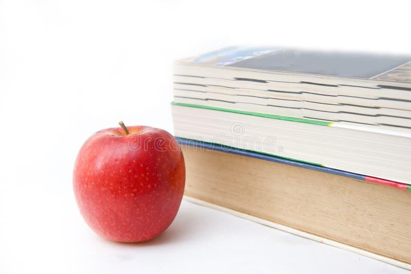 Livro e maçã no backgound branco imagem de stock