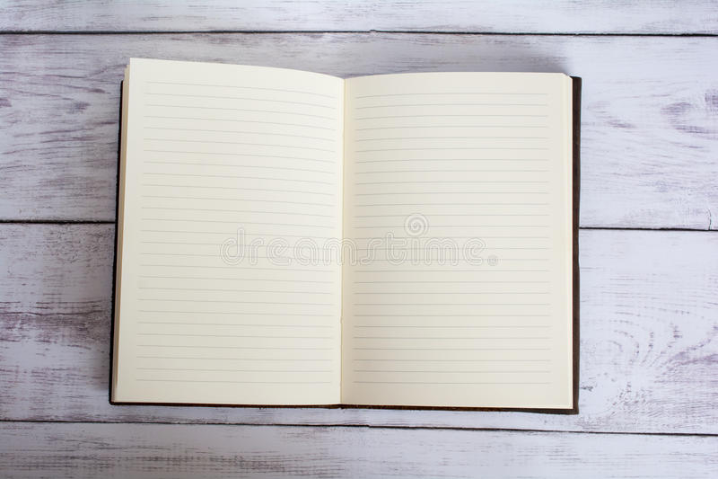 Livro encadernado do jornal do couro clássico aberto em um assoalho branco da placa do celeiro imagens de stock royalty free