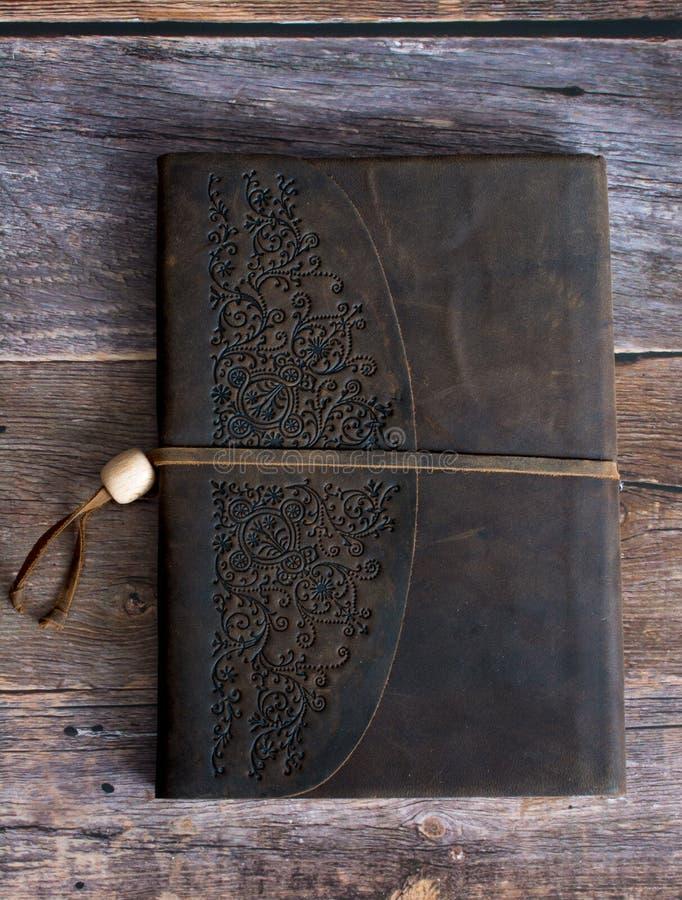 Livro encadernado do jornal do couro clássico em um assoalho velho da placa do celeiro diretamente imagens de stock royalty free