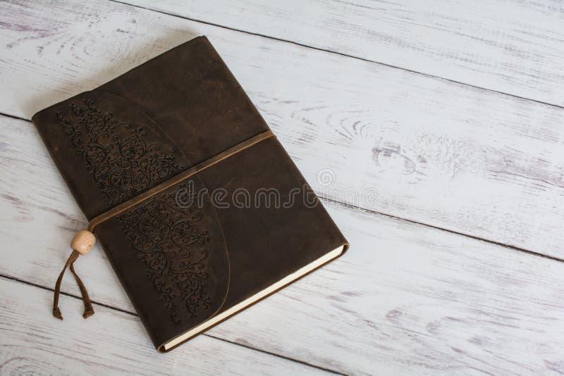 Livro encadernado do jornal do couro clássico em um fim branco do assoalho da placa do celeiro acima imagens de stock