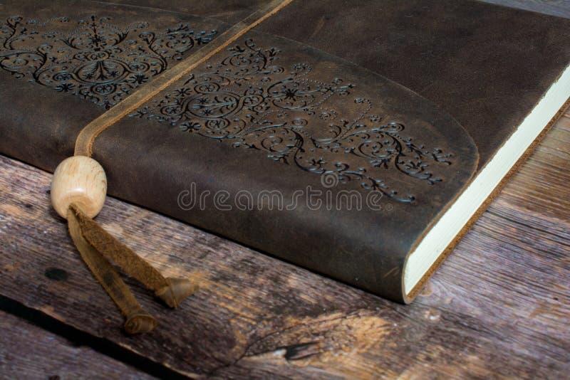 Livro encadernado do jornal do couro clássico em um fim velho do assoalho da placa do celeiro acima fotos de stock royalty free