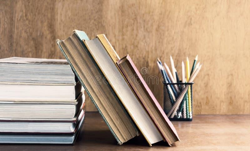 Livro encadernado velho e livro de texto empilhados na tabela de madeira O conce fotos de stock