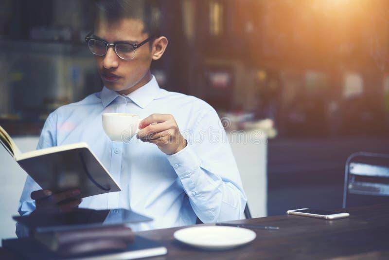 Livro favorito da leitura inteligente do indivíduo do moderno ao apreciar o cappuccino saboroso fotos de stock