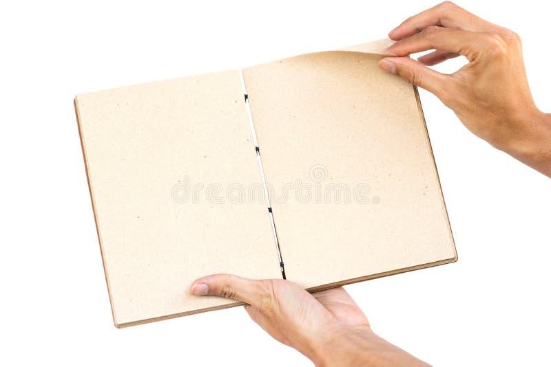 Livro feito à mão aberto da terra arrendada da mão isolado no fundo branco Trajeto de grampeamento imagens de stock