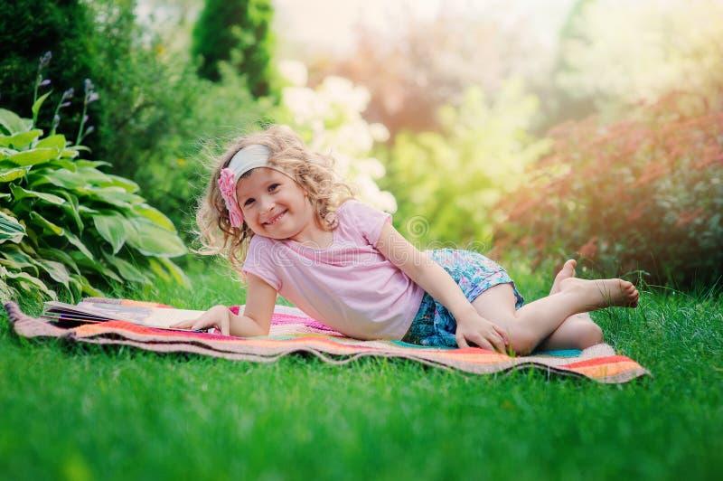 Livro feliz da aprendizagem e de leitura da menina da criança no jardim do verão fotografia de stock