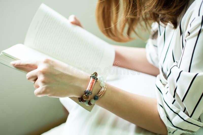 Livro holking da mão da mulher para ler fotografia de stock