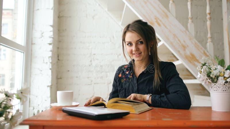 Livro lido de levantamento e de sorriso do estudante de mulher bonito novo no café dentro imagem de stock