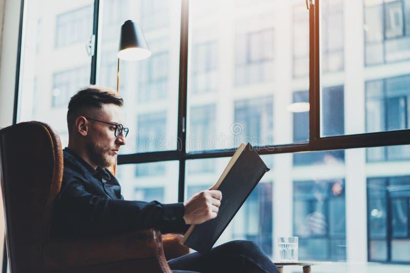 Livro negro à moda inteligente da leitura do homem de negócios ao sentar-se na cadeira do vintage em seu escritório moderno Homem imagens de stock