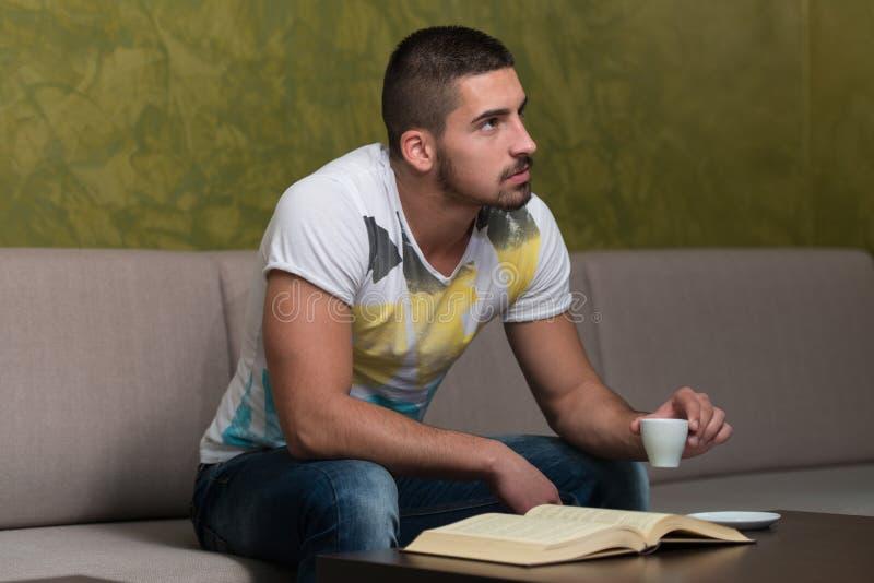 Livro novo de sorriso de In Cafe Reading do estudante imagem de stock royalty free