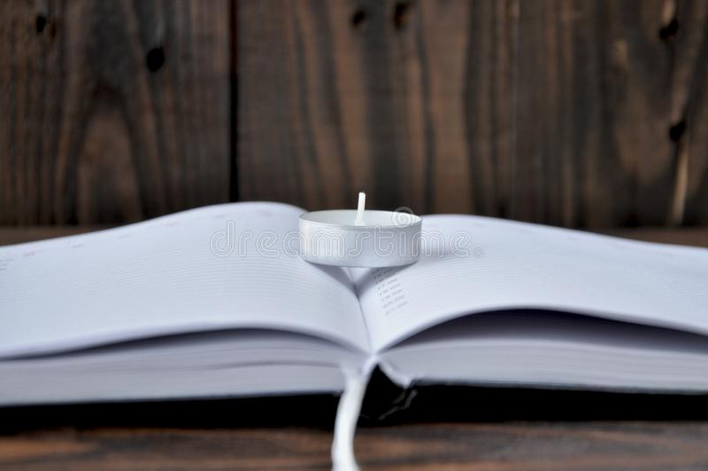 Livro ou caderno aberto No livro ? uma vela pequena foto de stock royalty free