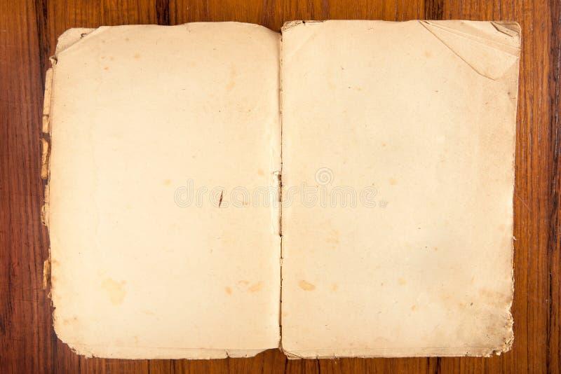 Livro softcover velho aberto em um fundo de madeira fotos de stock