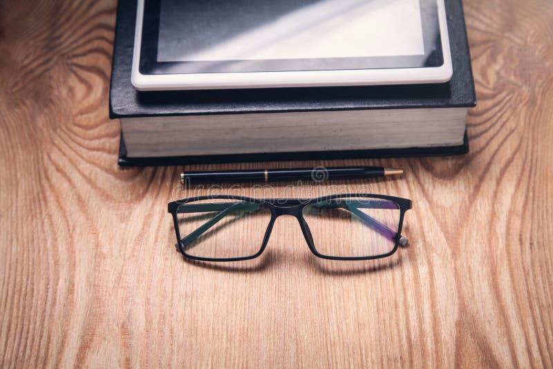 Livro, tabuleta, vidros na tabela de madeira Conceito de Ebook imagem de stock