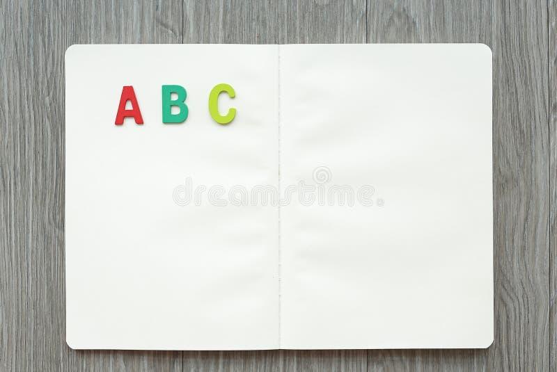 Livro vazio aberto com letras ABC na tabela de madeira Conceito da instru??o fotos de stock