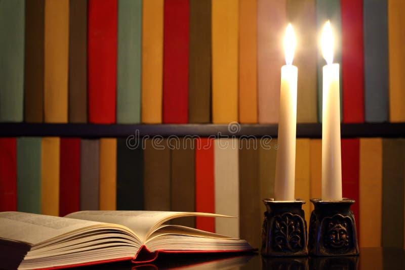 Livro, velas e bibliotecas abertos foto de stock