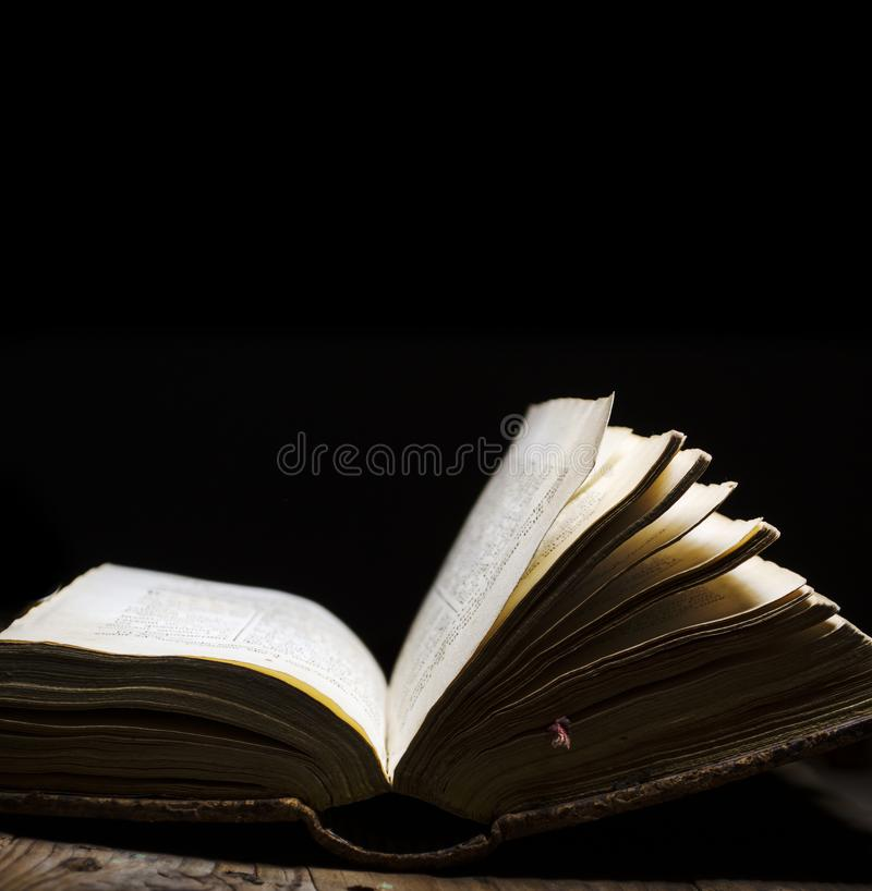 Livro velho aberto na tabela do vintage no fundo escuro A Bíblia lida e do estudo do vintage com página iluminada Literatura e ed fotos de stock