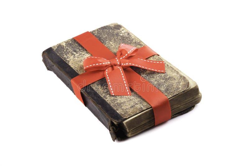 Livro velho como um presente com fita vermelha se isolou fotografia de stock royalty free