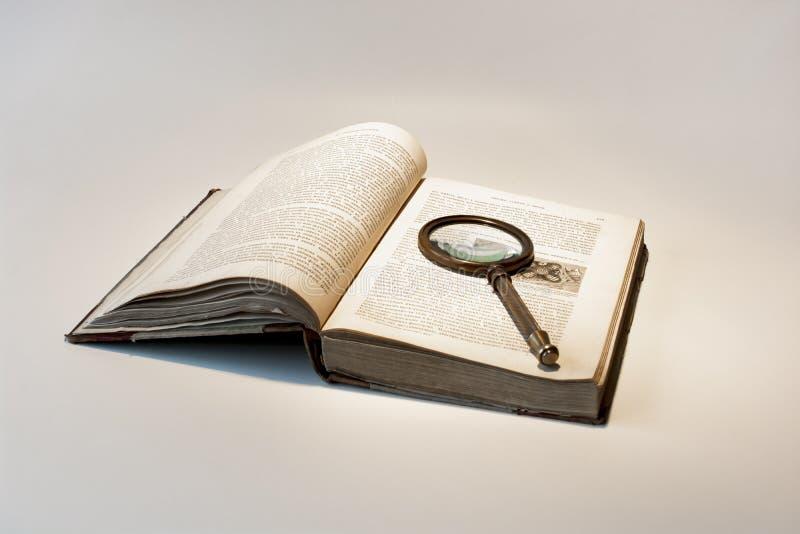 Livro velho e lente de aumento imagem de stock