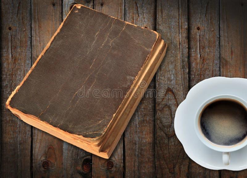 Livro velho e um cu do café na madeira imagens de stock royalty free