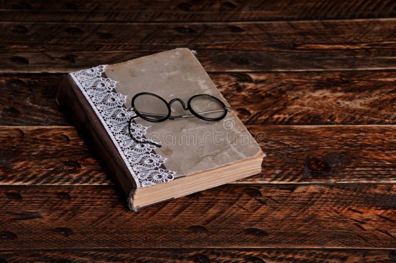 Livro velho e vidros de leitura redondos do vintage fotografia de stock royalty free