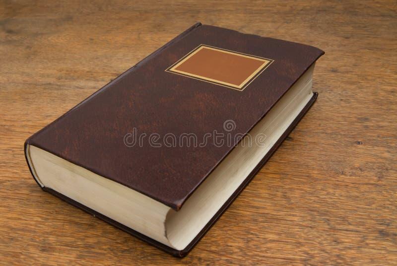 Livro velho fechado em uma tabela de madeira fotos de stock