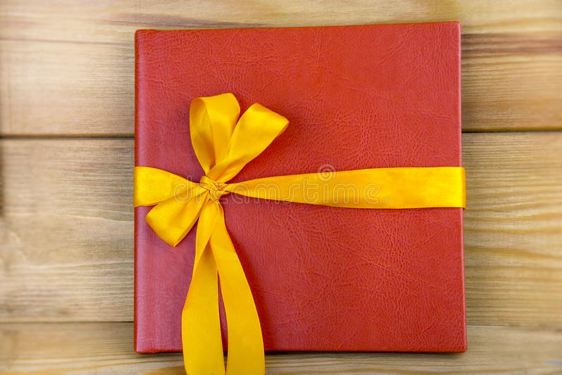 Livro vermelho com fita amarela Presente vermelho em um fundo de madeira imagem de stock royalty free