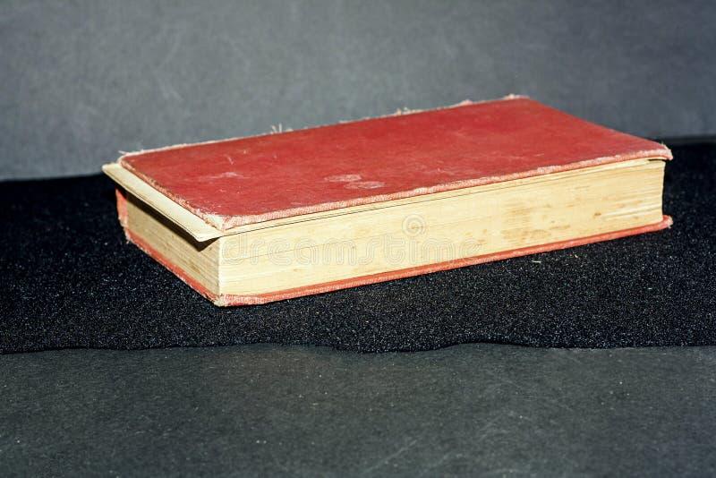 Livro vermelho velho com as páginas que caem distante fotos de stock