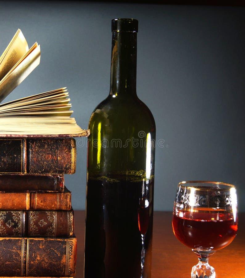 Livros antigos, um vidro do vinho tinto e garrafa foto de stock