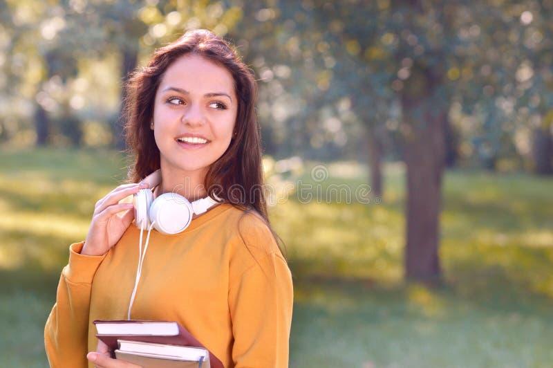 Livros bonitos e na moda novos e olhar da posse da menina do estudante de lado fotografia de stock royalty free