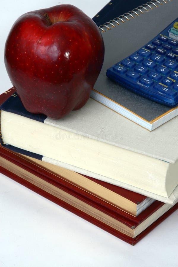 Livros, calculadora e maçã fotografia de stock