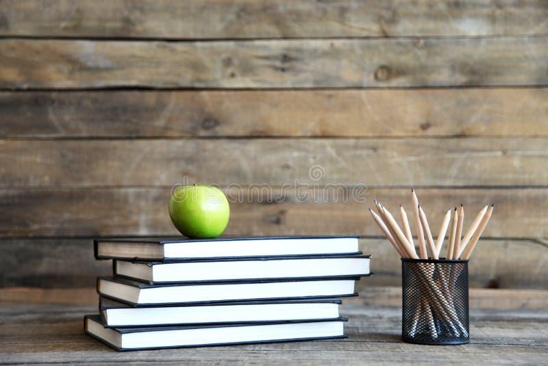 Livros com a maçã na tabela de madeira imagem de stock royalty free