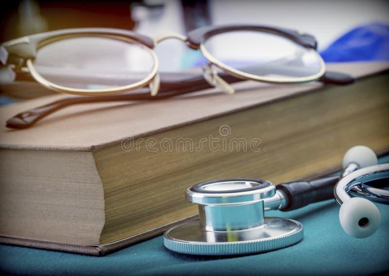 Livros da medicina ao lado do vintage e do estetoscópio das seringas fotografia de stock royalty free