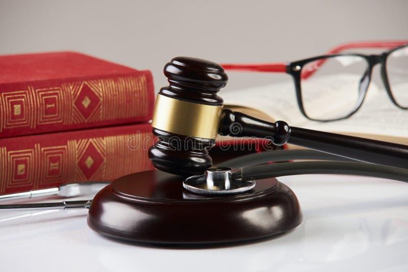 Livros de lei com o martelo de madeira dos juizes e o estetoscópio médico foto de stock royalty free