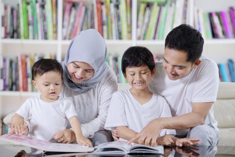 Livros de leitura asiáticos da família na biblioteca fotografia de stock royalty free
